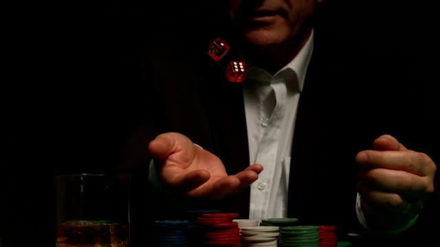 Cool gambler throwing red dice
