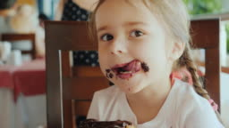A cool little girl is eating a sweet bun, her face is smeared with chocolate