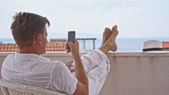 DS Cool man using smartphone on the balcony