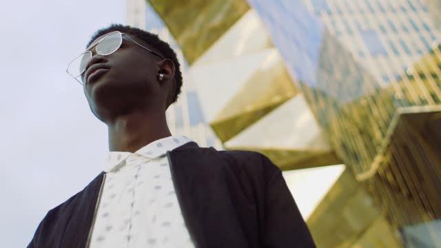 vídeos de stock e filmes b-roll de cool man wearing glasses outdoors - plano charriot