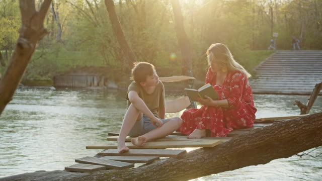 cool mother in her 40's and her 12 years old son sitting on tree house above a river reading a book and spending time together. - 12 13 years stock-videos und b-roll-filmmaterial