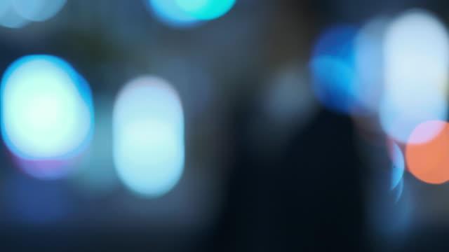 交通や通行人と都市夜景の 4 k クールなトーン デフォーカス ビデオ - 焦点点の映像素材/bロール