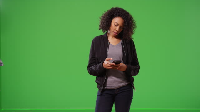 Cool woman in black jacket receiving text message on smart phone on greenscreen