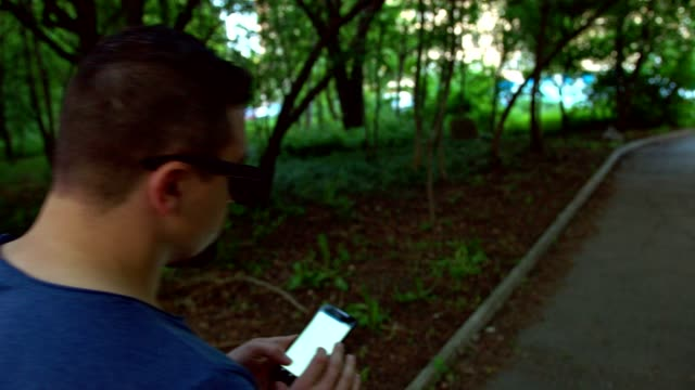 Cool young guy walking in the park and using his smart phone to text or browse the internet