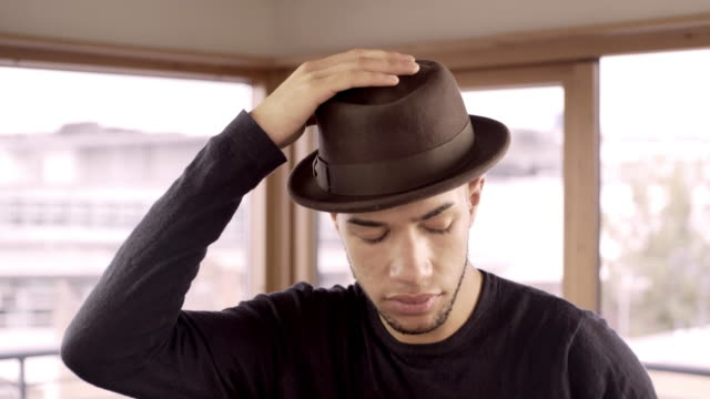 vidéos et rushes de a cool young man putting his hat on and taking it off. - chapeau