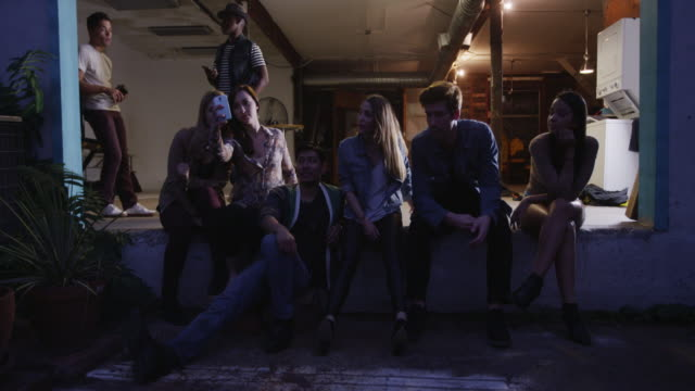 cool young multi ethnic group of friends sitting in loading bay at studio as fun party comes to an end - patio video stock e b–roll