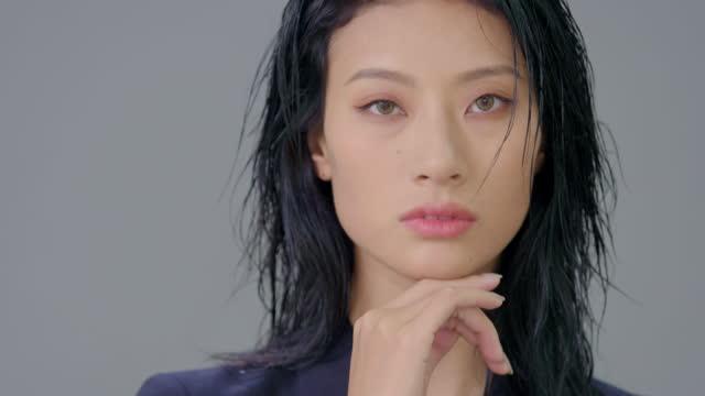 vidéos et rushes de cool young woman in suit,4k - main au menton