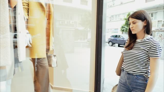 cool young woman looking at a store window. - window display stock videos and b-roll footage