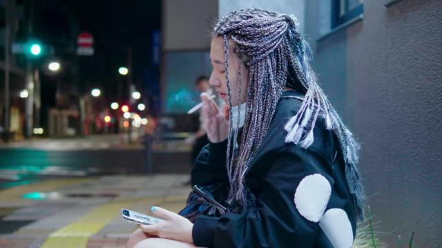 スマートフォンを使用してクールな若い女性 - 紙巻煙草点の映像素材/bロール