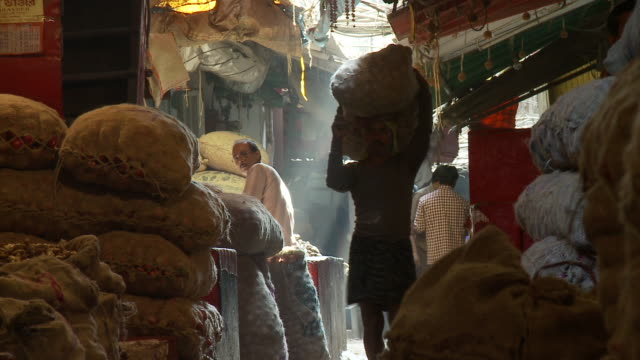 Coolies carry sacks through a spice market in Calcutta.