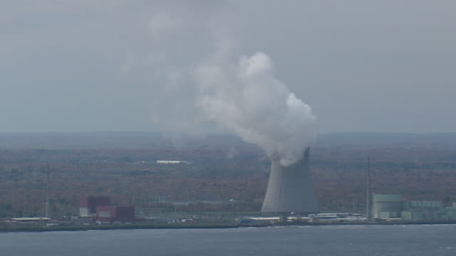 aerial cooling tower on shore of lake ontario billowing steam at nine mile point nuclear station / new york, united states - electrical component stock videos & royalty-free footage