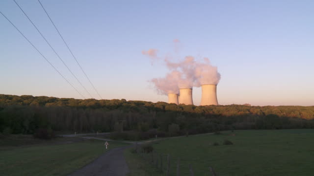 ws cooling towers of power station against blue sky / cattenom, lorraine mosel, france - lorraine bildbanksvideor och videomaterial från bakom kulisserna