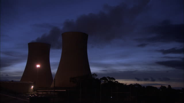 cooling towers release steam into the night sky. - power station stock videos & royalty-free footage