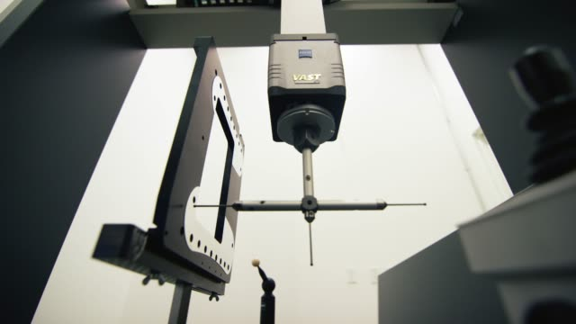 a coordinate measuring machine uses a ruby red torch probe to measure tolerances of parts in a manufacturing facility - micrometer stock videos & royalty-free footage