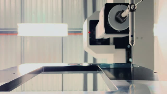 a coordinate measuring machine uses a torch probe to measure tolerances of parts in a manufacturing facility - measuring stock videos & royalty-free footage