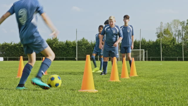 coordinated young footballer completing dribbling drill - allarme di prova video stock e b–roll