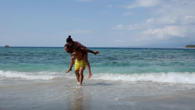 vídeos y material grabado en eventos de stock de coouple perder el tiempo en el agua en la playa de gili travangan - vestido parcialmente