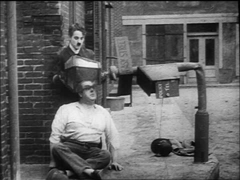 vídeos de stock, filmes e b-roll de b/w 1917 cop charlie chaplin holding bent street lamp over head of large seated man - charlie chaplin