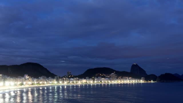 vídeos de stock, filmes e b-roll de lapso de tempo da paisagem do crepúsculo de copacabana - passar a frente