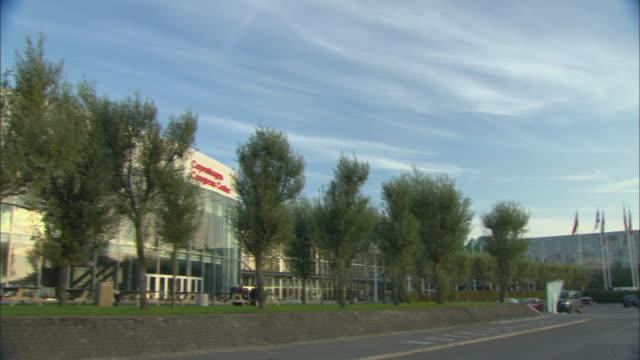 vidéos et rushes de ws pan copenhagen congress center with nearby parking lot lined with danish flags / copenhagen, denmark - facade