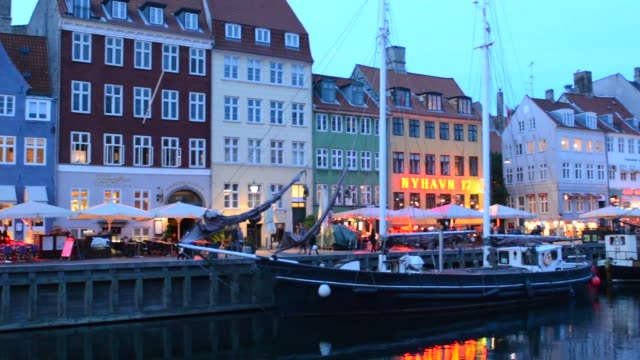 Copenhagen Denmark famous Nyhavn night exposure of color homes and boats with crouds Kobenhavn tourists