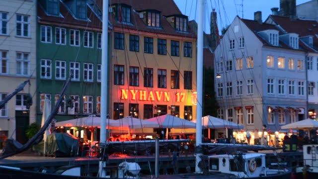 vídeos de stock, filmes e b-roll de copenhagen denmark famous nyhavn night exposure of color homes and boats with crouds kobenhavn tourists - letra maiúscula
