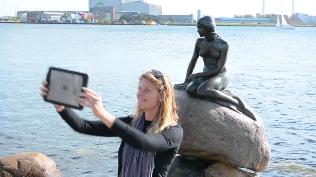 Copenhagen Denmark Little Mermaid monument Den Lille Havfrue with tourist woman taking photo Kobenhavn