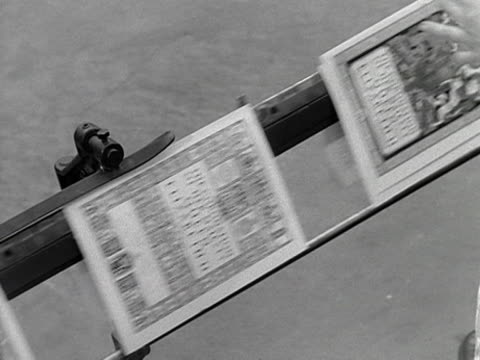 copies of the official souvenir coronation programme move along a conveyer belt at a printing works 1953 - coronation stock videos and b-roll footage