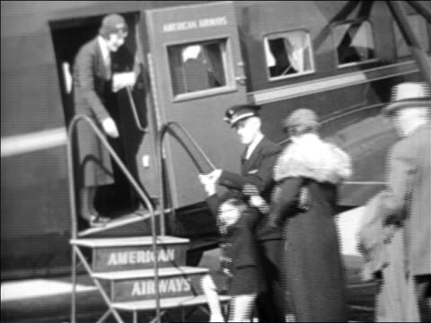 b/w 1933 co-pilot + female flight attendant welcoming passengers aboard american airlines airplane - anno 1933 video stock e b–roll