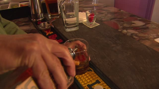 copper fiddle distillery owner mixes a drink made with craft liquor on june 30, 2014 near chicago, illinois. - absinth stock-videos und b-roll-filmmaterial