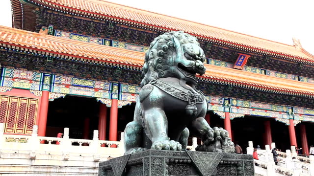 Copper lion before palace of Beijing Gugong in snow.