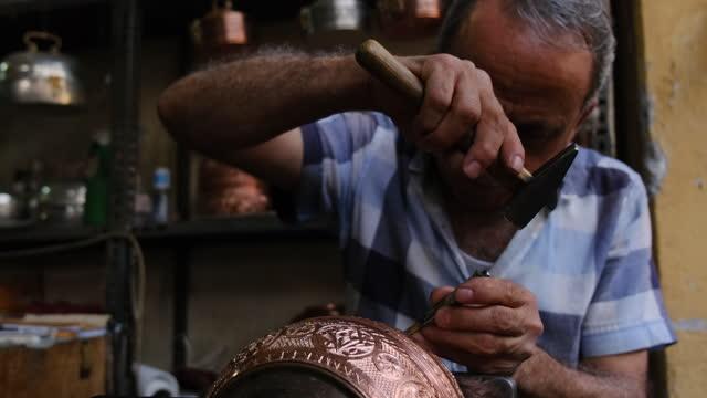 stockvideo's en b-roll-footage met coppersmith hameren ontwerp op koperen plaat - messing about