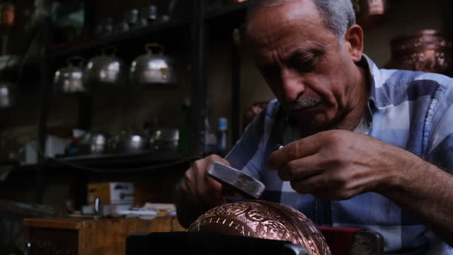 coppersmith hammering design on copper plate - craftsperson stock videos & royalty-free footage