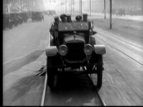 ms, b&w, cops cars and fire engine driving fast on street, 1930's  - 無声映画点の映像素材/bロール