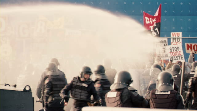 Cops spraying protesters with a pressure sprayer during a riot.