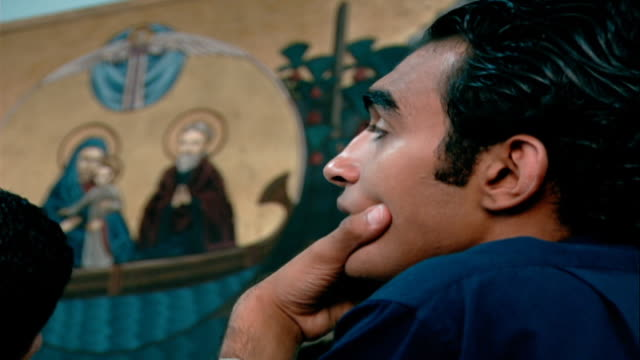 copts. medium on the face of a coptic man listening to prayers with a painted icon of baby jesus, mary, and joseph on the wall beside him. - credente video stock e b–roll