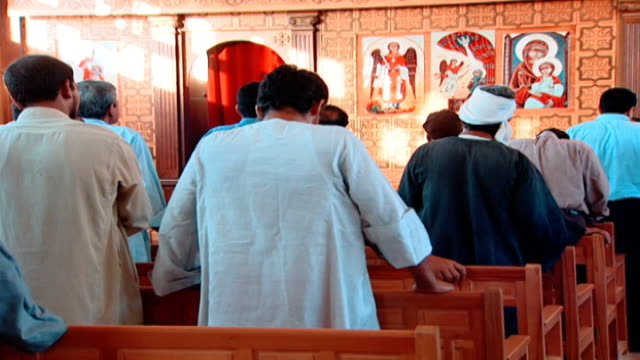 stockvideo's en b-roll-footage met copts mls of male worshippers standing in pews facing the iconostasis and praying in the orans posture - gelovige