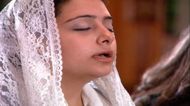 copts cu on a female worshipper wearing a lace headscarf and reciting prayers with her eyes closed during mass services copts make up 1015 percent of... - eyes closed stock videos & royalty-free footage