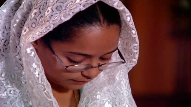 copts cu on the face of a female coptic worshipper her head covered in a lace scarf reciting prayers in church copts make up 1015 percent of egyptians - worshipper stock videos & royalty-free footage