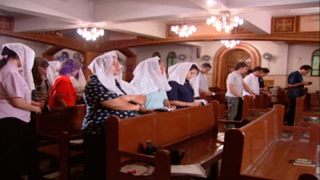 copts. pr across worshippers standing in pews reciting prayers during mass. copts make up 10-15 percent of egyptians. - 信者点の映像素材/bロール