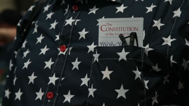 a copy of the constitution of the unites states sits in the pocket of a member of public as people watch the independence day parade on july 4 2019... - constitution stock videos and b-roll footage