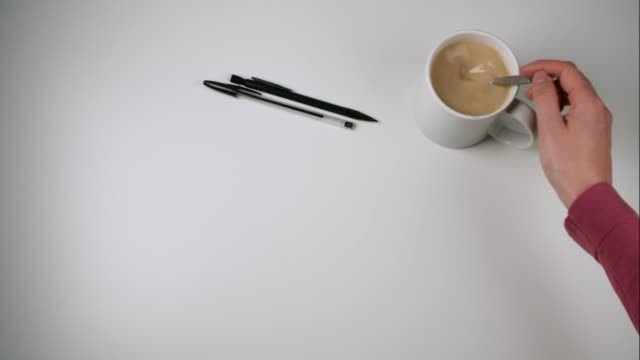 stockvideo's en b-roll-footage met copy space on desk with coffee being stirred and pens - table top shot