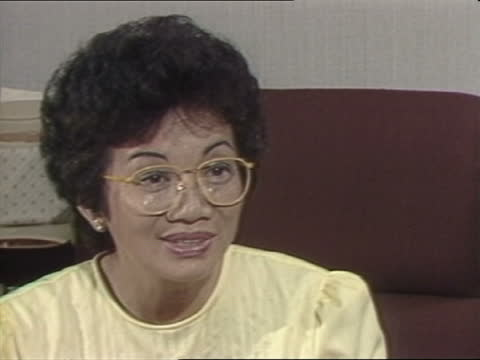 stockvideo's en b-roll-footage met corazon aquino interview; philippines: manila: int cory aquino shakes john suchet, walks l-r to sit at desk cms portrait cory and assassinated... - crime and murder