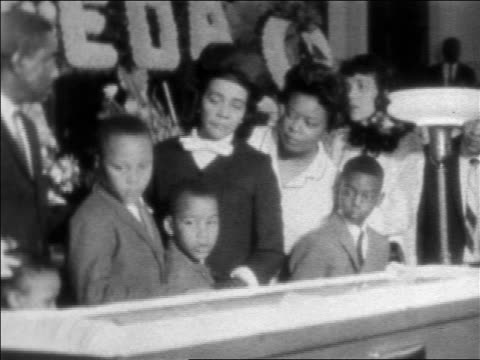 Coretta Scott King family by open casket of Martin Luther King during funeral / newsreel