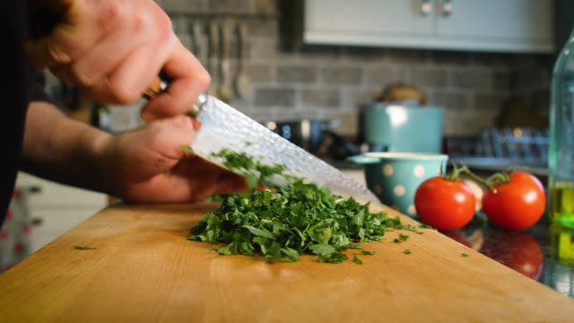 coriander is cut on chopping board - cutting board stock videos and b-roll footage