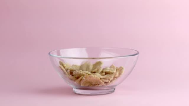 vidéos et rushes de flocons de maïs ou céréales tombant sur un récipient en verre. préparer un repas sain. - céréale