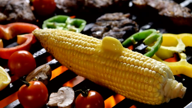 Corn with melting butter on the flaming grill