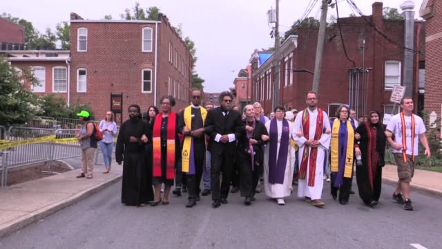 cornell west and interfaith clergy link arms arrive for peaceful protest, they pray and sing as white supremacists arrive. - clergy stock videos & royalty-free footage