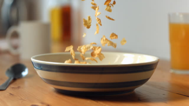 CU SLO MO Cornflakes being poured into bowl (bowl and spoon placed on table  breakfast scene) / Manchester, United Kingdom