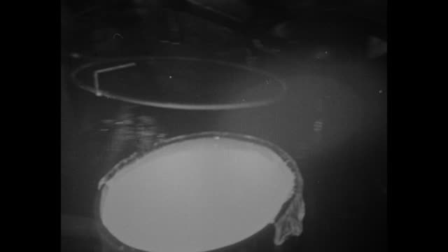 stockvideo's en b-roll-footage met corning glass works worker in protective gear knocks excess off of large scoop of molten glass during casting of a 200inch mirror for use at the... - handen in een kommetje
